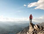 man standing on mountain clouds horizon overview hiking